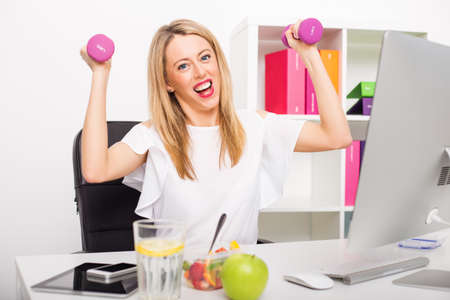 staying: Happy woman in office being active Stock Photo