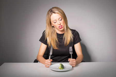 a portion: Woman on diet eating broccoli Stock Photo