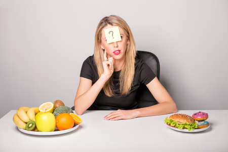 Woman with sticky note and question mark on her forehead choosing between healthy and unhealthy foods Stock Photo