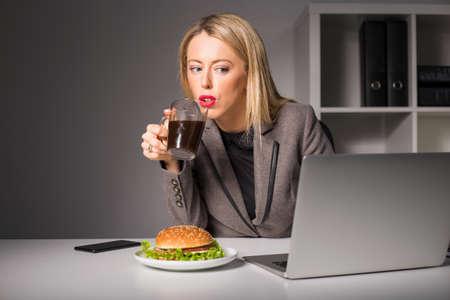 negocios comida: Mujer que trabaja y que tiene café y hamburguesas para el almuerzo