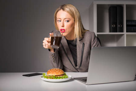 junk food: Woman working and having coffee and burger for lunch Stock Photo