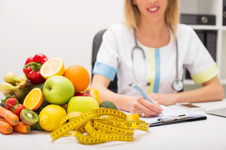 weight loss plan: Tape measure and vegetables on doctors table Stock Photo