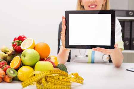 nutrition: Tape measure, vegetables, and doctor holding tablet with blank screen