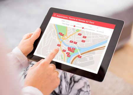 Persona in cerca di luoghi di soggiorno su tavoletta digitale app