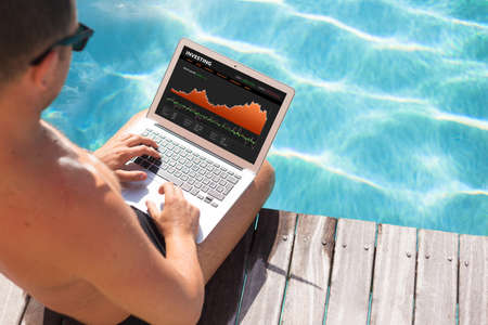 stock quotes: Investor looking at stock quotes on laptop by the pool Stock Photo