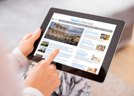 read magazine: Sample news website on digital tablet. Contents are all made up
