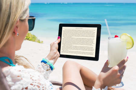 girls at the beach series: Womanreading  on tablet computer Stock Photo