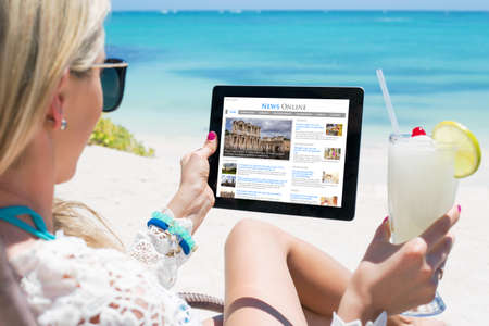 Woman reading news on tablet while relaxing on the beach. Contents are all made up.