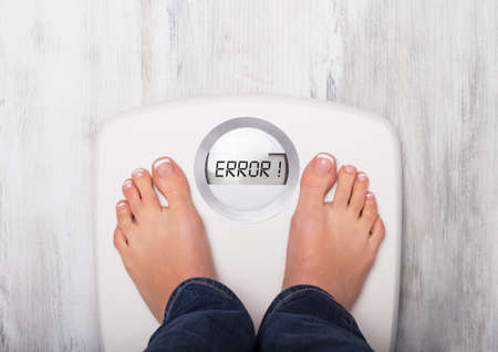 error message: Woman standing on weight scale showing error message