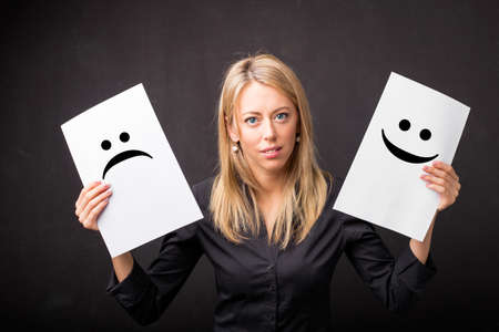 dual: Woman holding sheets with sad and happy smileys