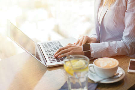 savvy: Woman in cafe working on computer Stock Photo