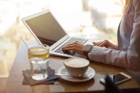 Woman drinking coffee and working on laptop Stockfoto