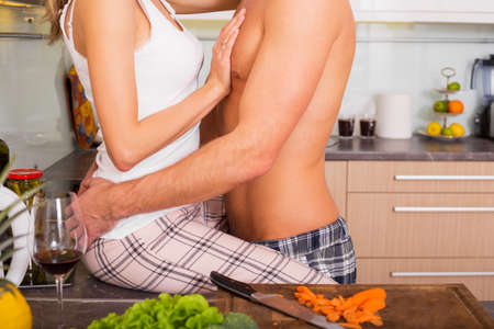 Foreplay in the kitchen while cooking Stock Photo