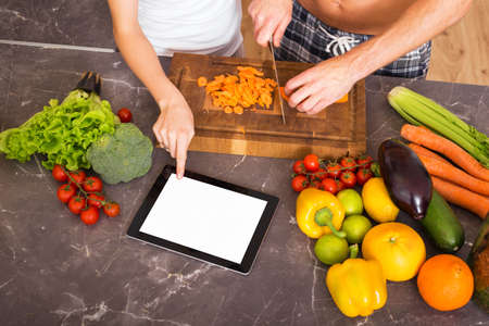 people cooking and using tablet