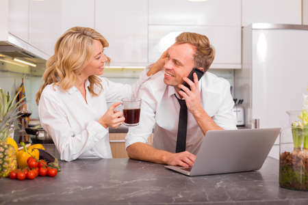 man at work: Woman and man in kitchen before going to work Stock Photo