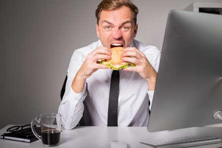 eating food: Hungry man at the office eating burger