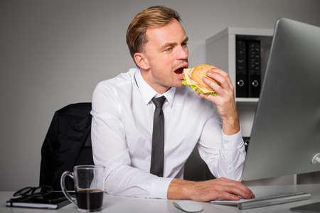 work stress: Man eating burger and working