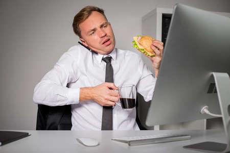 Bezige mens op het kantoor met koffie en burger