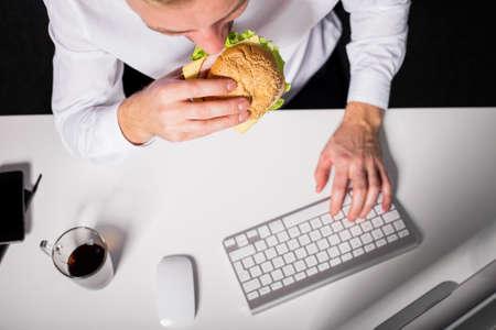 El hombre que come el almuerzo poco saludable