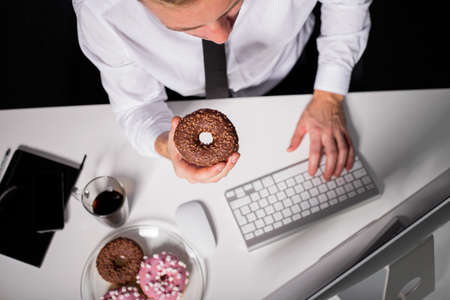 cravings: Man at the office eating donuts