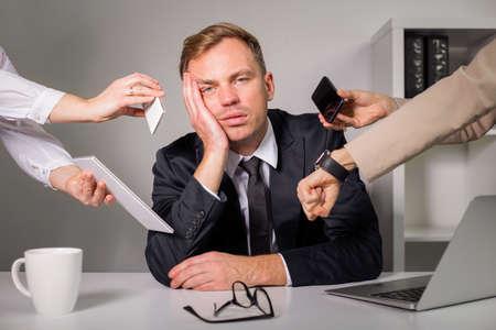 muchas personas: El hombre cansado de ser sobrecargado en el trabajo