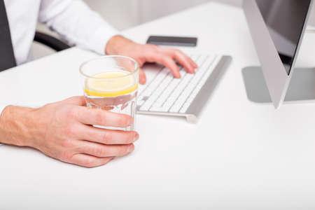 still water: Man at the office drinking lemon water Stock Photo
