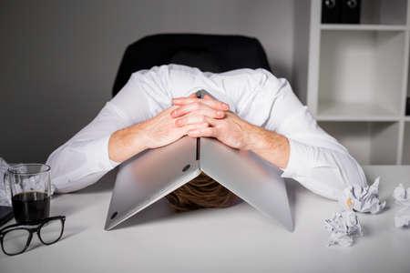 agotado: Hombre que oculta bajo la computadora portátil
