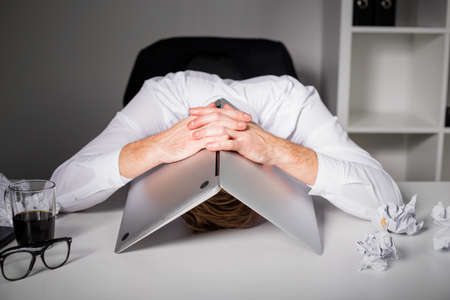 business men: Man hiding under laptop Stock Photo