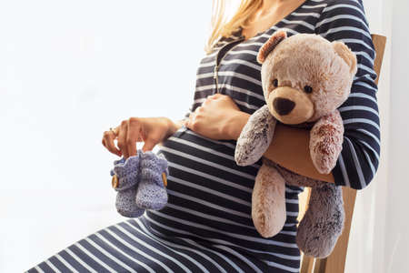 unborn: Pregnant woman holding baby boots and teddy bear