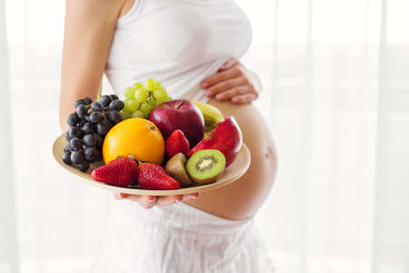 fruit plate: Pregnant woman holding fruit plate