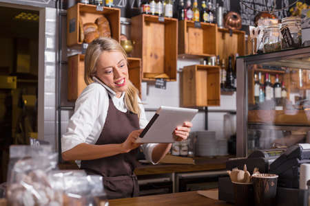 Female barista talking on the phone and using tablet while standing behind the counter Reklamní fotografie - 55359986