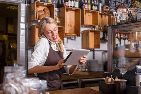 Vrouwelijke barista praten over de telefoon en het gebruik van tablet tijdens het staan achter de toonbank