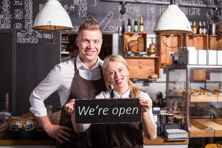 열린 표지판을 보여주는 커피 숍 소유자