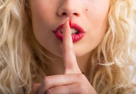 Vrouw die haar vinger tegen haar lippen Stockfoto