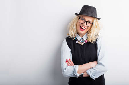 people laughing: Hipster woman leaning against the wall with crossed hands