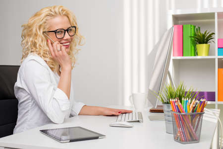 Office women: Woman in office talking on the phone while using computer Stock Photo