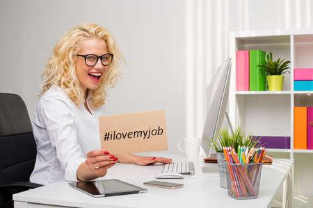 """Vrouw in bureau met """"Ik hou van mijn werk"""" karton Stockfoto"""