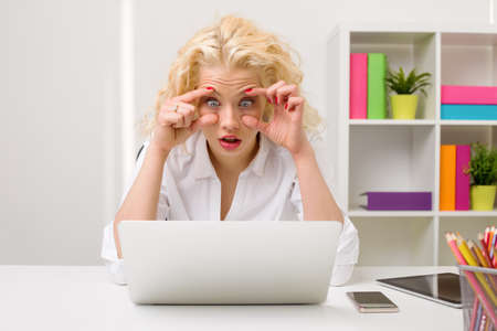 eyes open: Tired woman at the office looking at computer and holding her eyes open