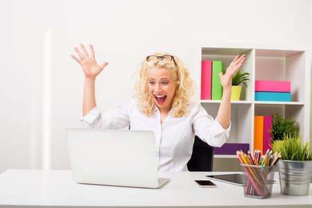Mujer sorprendida y feliz en la oficina que muestra su entusiasmo