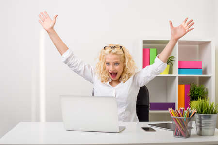 Woman at the office showing excitement and happiness Stock Photo