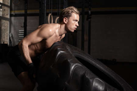man pushing: Fitness man pushing tire to build strength