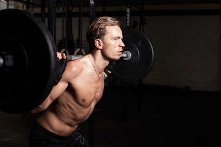 snatch: Fit man in gym lifting weights