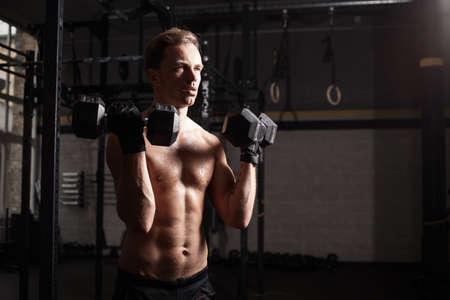cuerpo hombre: Hombre apto en las pesas de gimnasia de elevación