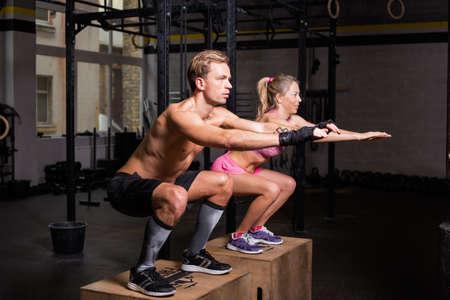fitness hombres: coueple ajuste que hace escuadrones en las cajas Foto de archivo