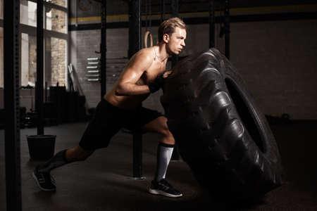 man pushing: Man pushing tire in gym Stock Photo