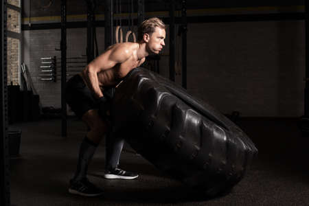 fitness hombres: el hombre fuerte y en forma de neumático que empuja Foto de archivo