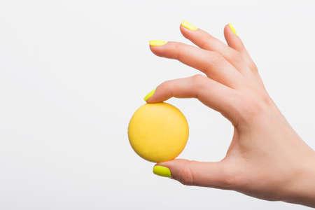 tastes: Person holding yellow macaroon Stock Photo