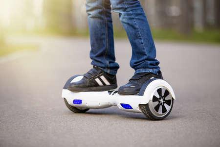 Menino, scooter elétrica ao ar livre Imagens