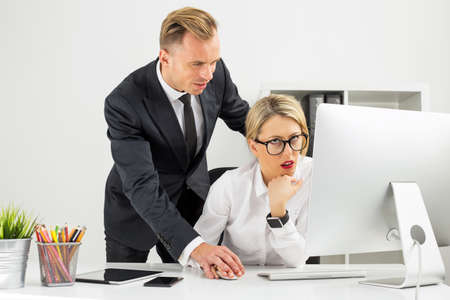 annoyed: Office employee being annoyed by her boss Stock Photo