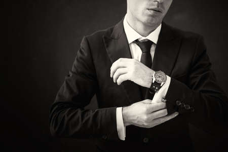 Black and white picture of business man fixing his shirt